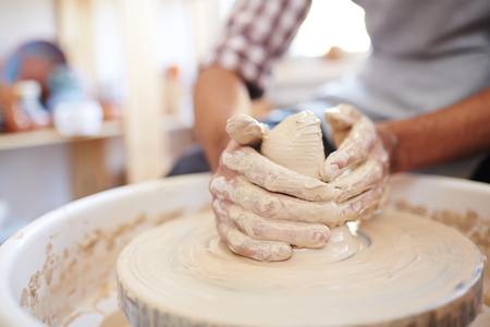 Close-up view of unrecognizable craftsman making clay pot on spinning pottery wheel in workshop