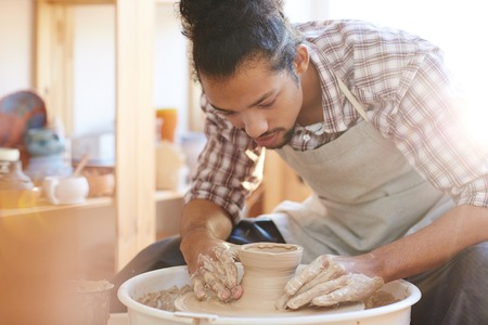 Portrait of young handsome mixed race male potter making clay pot on spinning pottery wheel in workshop