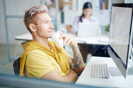 Designer sitting at his workplace drinking coffee and looking at computer monitor