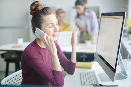 Businesswoman talking on the phone while sitting at the computer screen