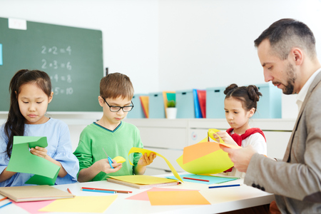 Primary school child sitting in classroom and making origami with male teacher while having after school class Фото со стока
