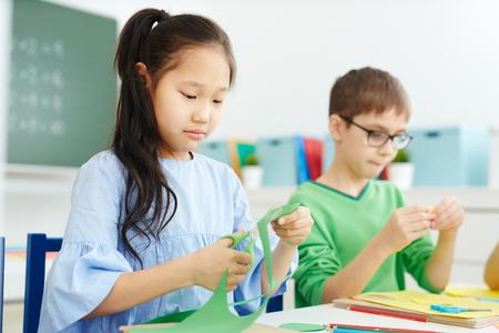 Kleines asiatisches Mädchen und kaukasischer Klassenkamerad, der Papier mit der Schere schneidet, während Origami auf Kunstunterricht in der Schule macht