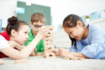Multiethnic group of primary school children sitting on floor in classroom and playing wooden block game during break