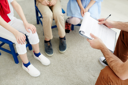 Unrecognizable male teacher holding clipboard with lesson plan and communicating with kids in classroom