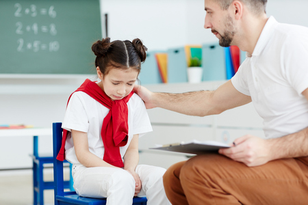 Pretty little girl sitting in classroom and crying because of bad mark while professional male teacher comforting her