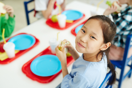 Pretty asian girl sitting at table with classmates in primary school canteen, cheerfully eating sandwich Stock Photo