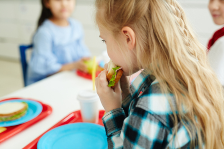 Little schoolgirl with beautiful blond hair eating tasty sandwich while sitting at table with classmates at elementary school cafeteria Stok Fotoğraf