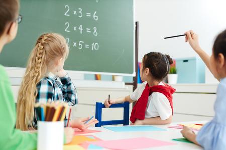 Basisschoolkinderen zitten in de klas en kijken naar schoolbord met vermenigvuldigingsbedragen Stockfoto