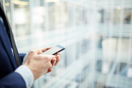 Hands of businessman with smartphone messaging by window of contemporary office center