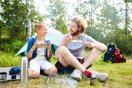 Father and son going camping have a quick lunch Imagens