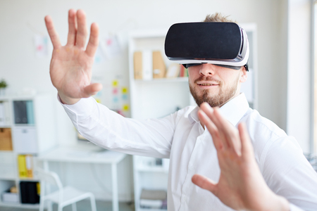 Businessman in Virtual Reality Glasses Orienting in Space at Office