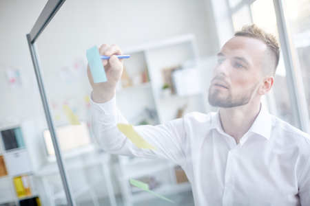 Businessman writing his ideas on an adhesive note on office window
