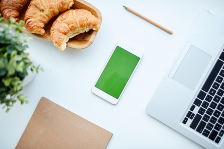Top view of smartphone, croissant and laptop on office table Stock Photo