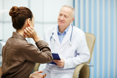 Rear view of nervous female patient with hair bun scratching neck while being interviewed by doctor in clinic Stockfoto