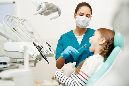 Serious concentrated young female dentist in mask and gloves examining childrens teeth in dental room