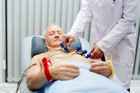 Serious senior male patient lying on table and waiting while medical technician removing electrodes from his chest after electrocardiogram procedure