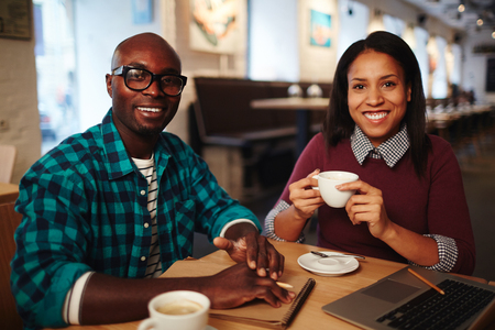 Portrait of black man and mixed race woman sitting at cafe table with laptop, drinking coffee and smiling happily at camera Foto de archivo - 102388132