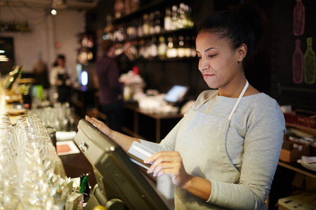 Young pretty mixed race waitress standing at cash counter and processing customer order in POS system Standard-Bild