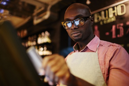 Low angle view of handsome black male waiter in glasses using POS system while working in restaurant Stock Photo