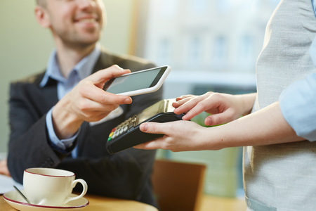 Unrecognizable waitress holding payment terminal while defocused male customer paying for drink with smartphone, close-up view Standard-Bild