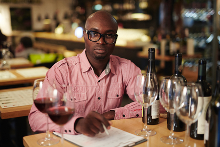 Portrait of confident black man in glasses looking at camera while sitting at table with wine bottles and doing paperwork