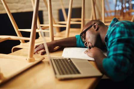 Tired black man in glasses sleeping on table near laptop in closed restaurant after working all day long