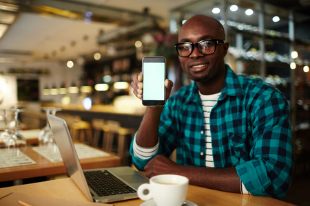 Portrait of young handsome man in casual clothes sitting at table with laptop, holding smartphone and looking at camera Foto de archivo - 102388386