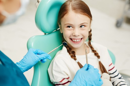 Cheerful excited pretty redhead girl with braids smiling at unrecognizable dentist with dental instrument in hands