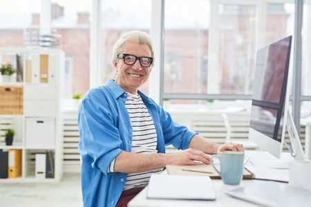 Portrait of attractive elderly man in casual wear sitting at office desk with computer and smiling at camera happily Stock Photo - 102388442