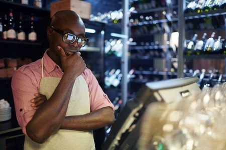 African American male standing at cash counter and looking at computer screen with POS system thoughtfully