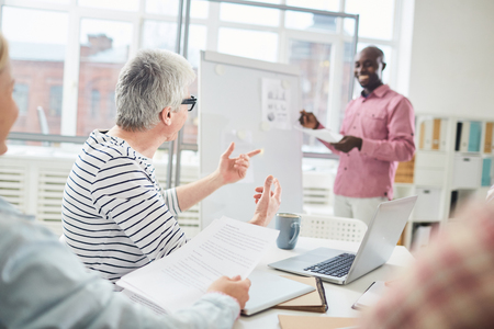 Defocused black man presenting creative ideas on whiteboard and smiling while brainstorming with colleagues in office Stock Photo