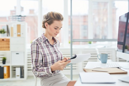 Young pretty caucasian woman sitting at office desk and reading paper on clipboard Reklamní fotografie - 102388449