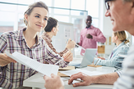 Young pretty female office worker discussing agreement with male colleague and smiling during business meeting
