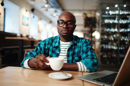 African American man in casual clothes sitting in cafe using laptop, drinking coffee and looking at camera on blurred background Foto de archivo - 102388455