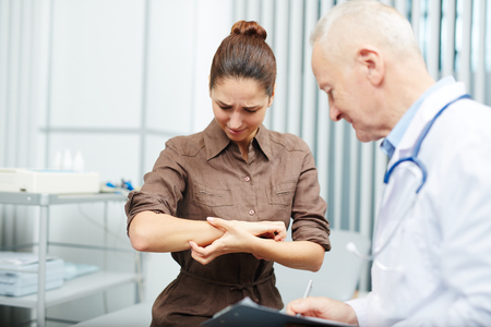 Distraught nervous frowning young woman scratching arm from stress and having itching, senior doctor holding checkup in office
