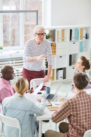Mature boss giving instructions to multiethnic group of young office managers while having meeting in conference room Stock Photo