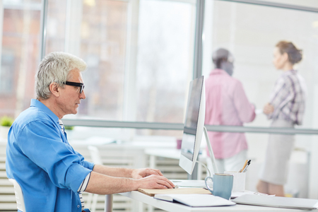 Side view of mature gray-haired Caucasian man in glasses sitting at desk and working on computer in modern office
