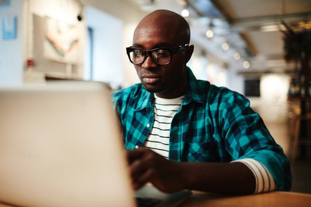 Black man in glasses and casual wear sitting in cafe and working on laptop on blurred background Foto de archivo - 102388769
