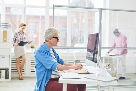 Side view of gray-haired Caucasian man working on computer while sitting at desk in white modern office Stock Photo