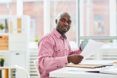 Portrait of handsome African American man sitting at office desk with documents and smiling at camera Foto de archivo - 102388957