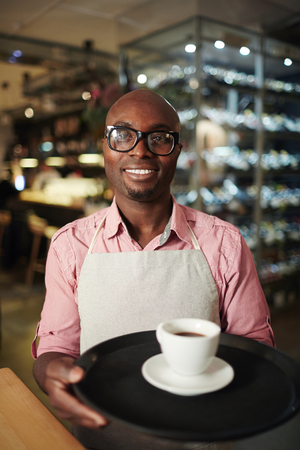 Portrait of African American male waiter in glasses holding a tray with fresh espresso and smiling at camera cheerfully Standard-Bild - 102388978