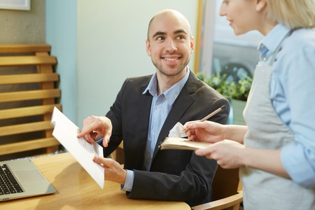 Young Caucasian male guest sitting at cafe table with menu, ordering meal and smiling to waitress cheerfully Фото со стока