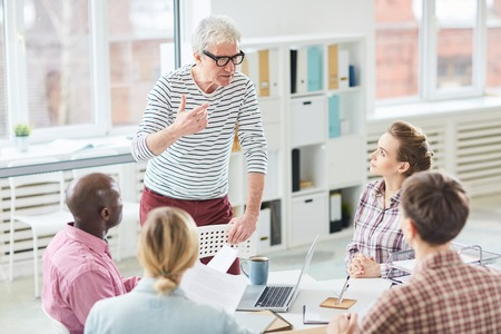 Mature Caucasian manager sharing his ideas with new colleagues while having brief in office