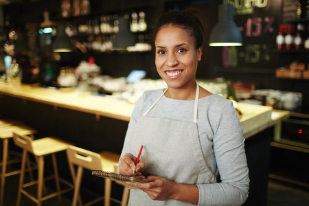 Portrait of pretty mixed race waitress standing against cash register, holding notepad and smiling at camera cheerfully