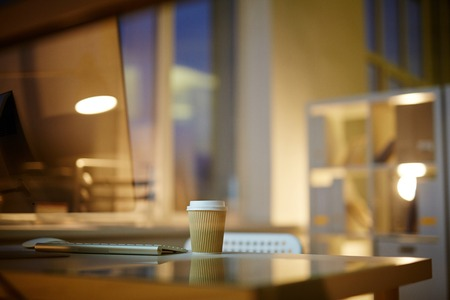 Interior of modern dim office: desk with computer and cup of coffee on foreground, panoramic windows on background 版權商用圖片