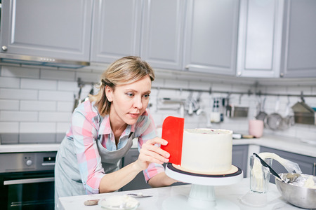 Young attractive caucasian woman in apron preparing smoothing delicious frosted cake in kitchen