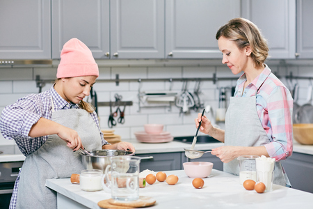 Professional female confectioners whisking eggs and sifting flour through sieve while making cake in modern kitchen