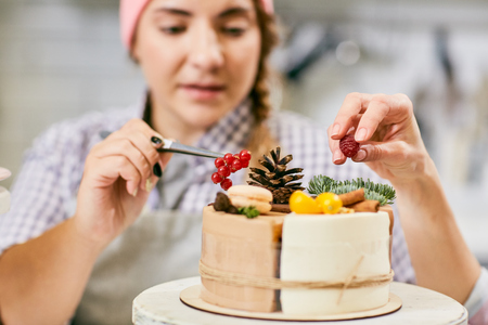 Defocused young female pastry chef decorating tasty cake with twigs, cones, currants and raspberries, close-up view Standard-Bild
