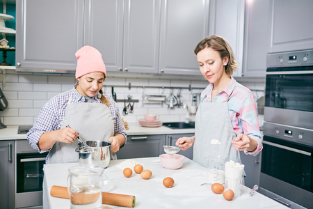 Young Caucasian women whisking eggs and sifting flour through sieve while cooking dessert in modern kitchen Stock Photo