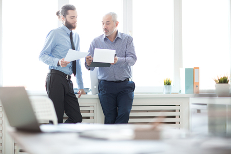 Two businessmen with documents standing at office and discussing new plans Stock Photo